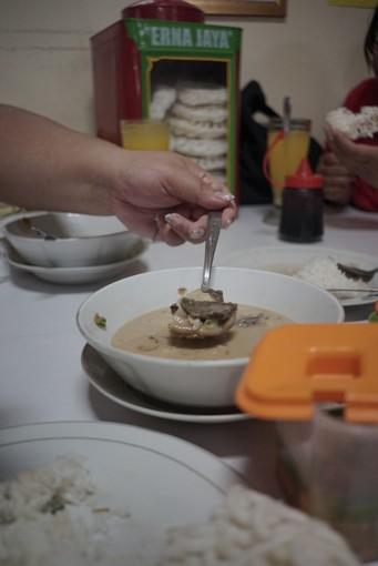 Kuliner Legendaris Cikini : Tangan kiri mengangkat sendok yang berisi daging soto betawi