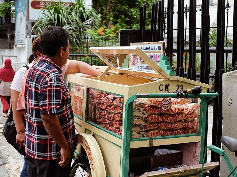Kuliner Legendaris Cikini : Pedagang sedang menbuka gerobak dagangannya yang penuh berisi roti